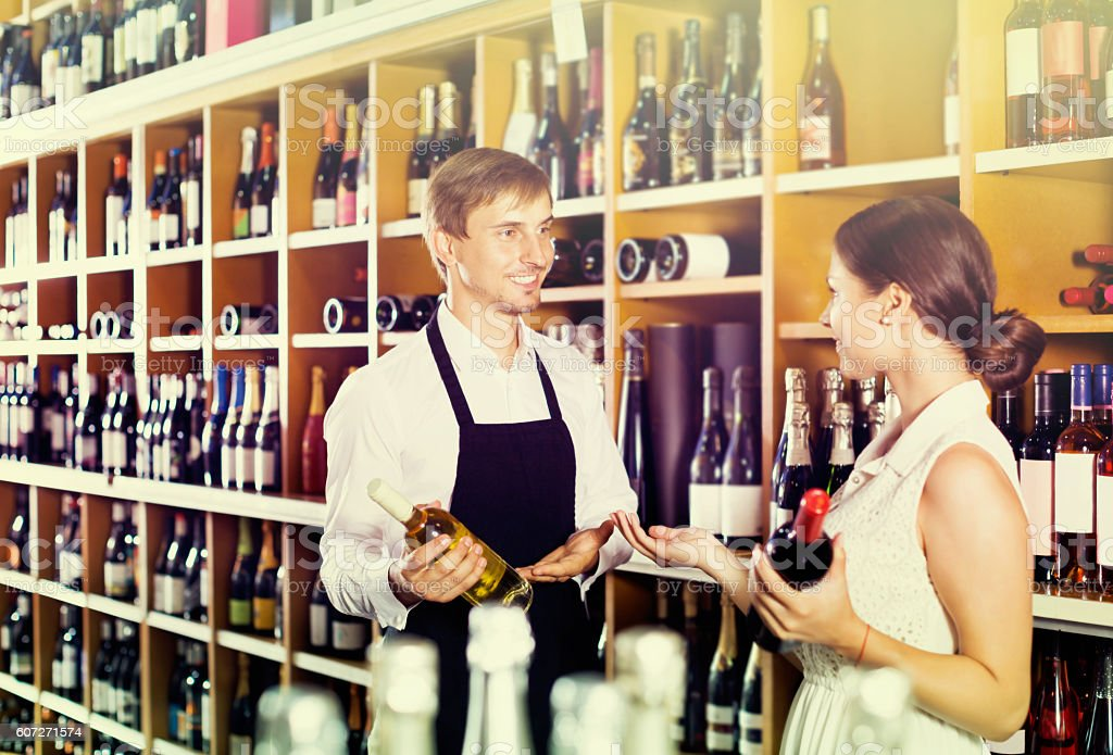 Seller helping woman customer with bottle of wine stock photo