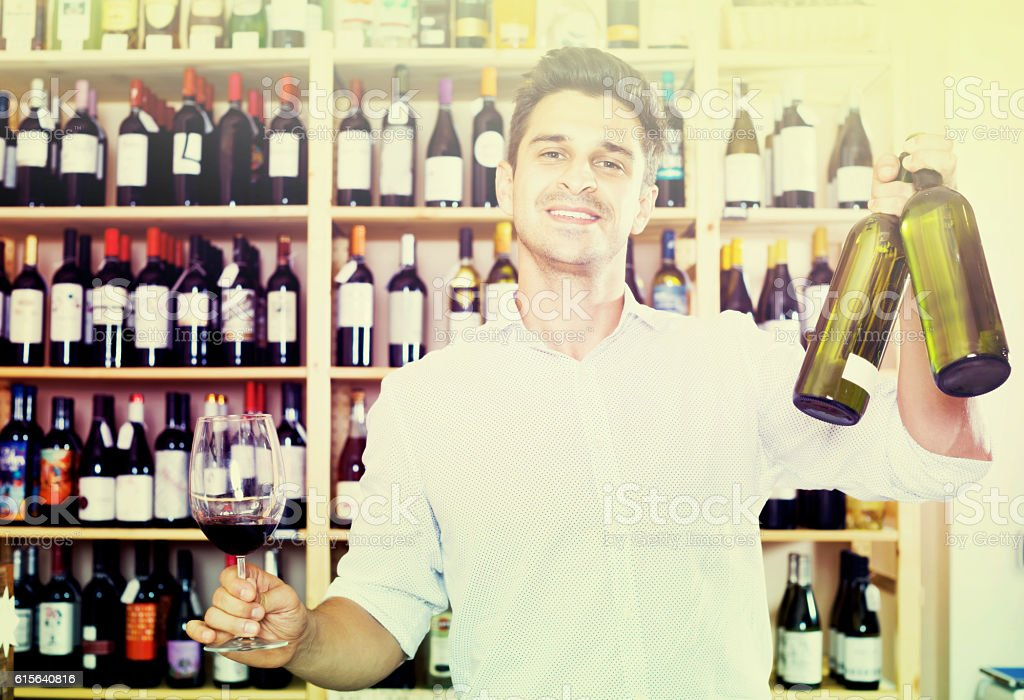 Seller holding bottle of wine stock photo