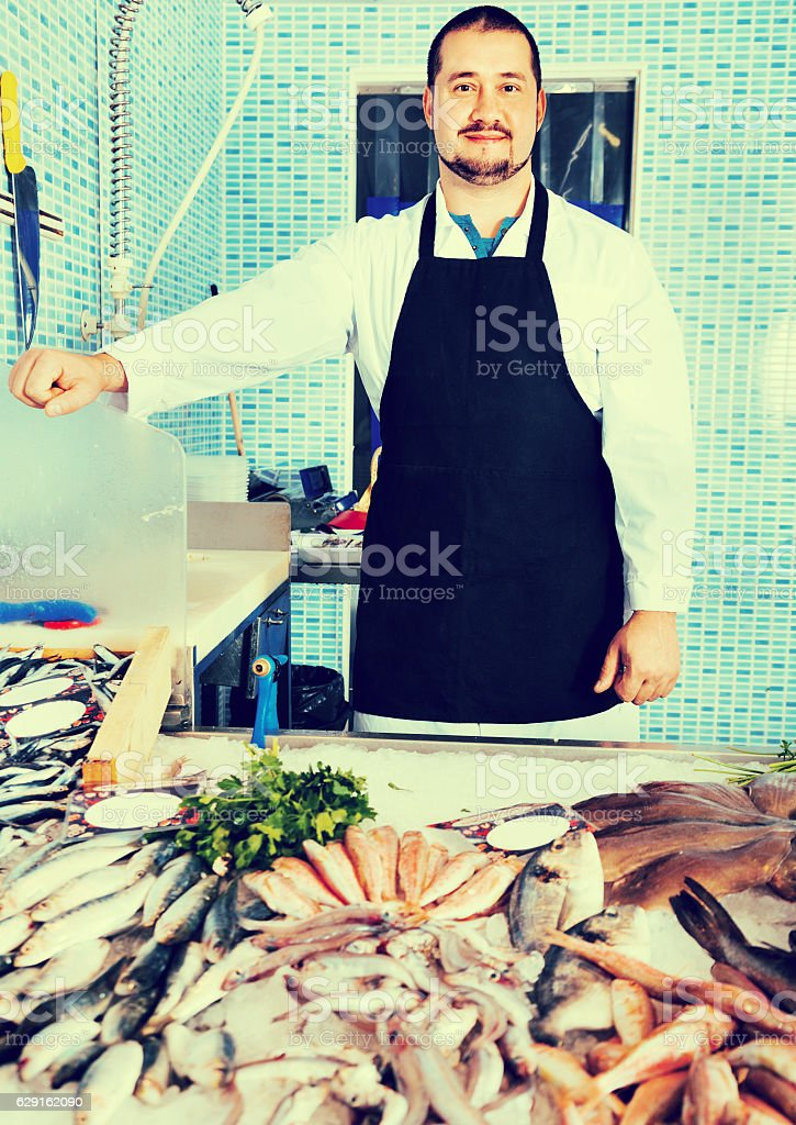 Seller in black apron shows fish counter stock photo