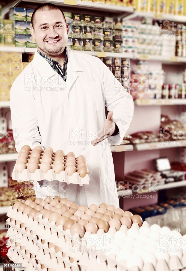 Seller posing with dozens of eggs stock photo