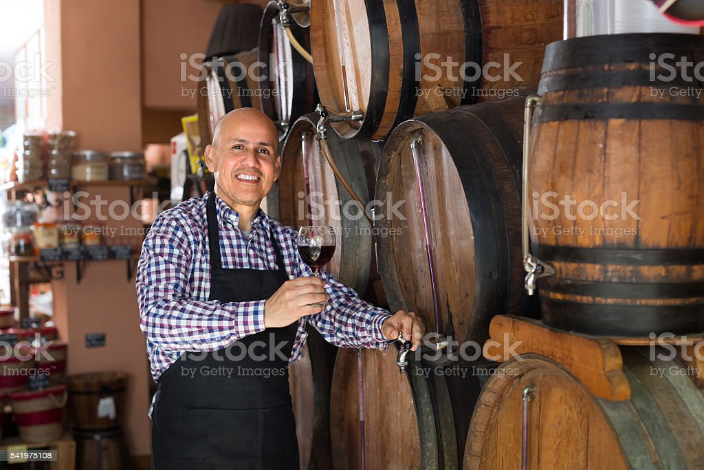 Seller pouring wine from wood barrel stock photo