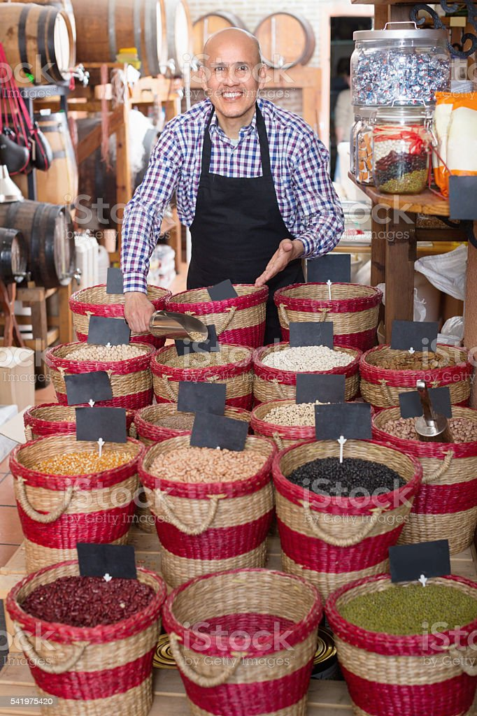 Seller showing dried beans on bazar stock photo
