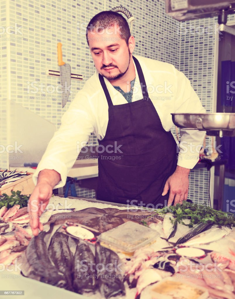 Seller showing fish lying stock photo