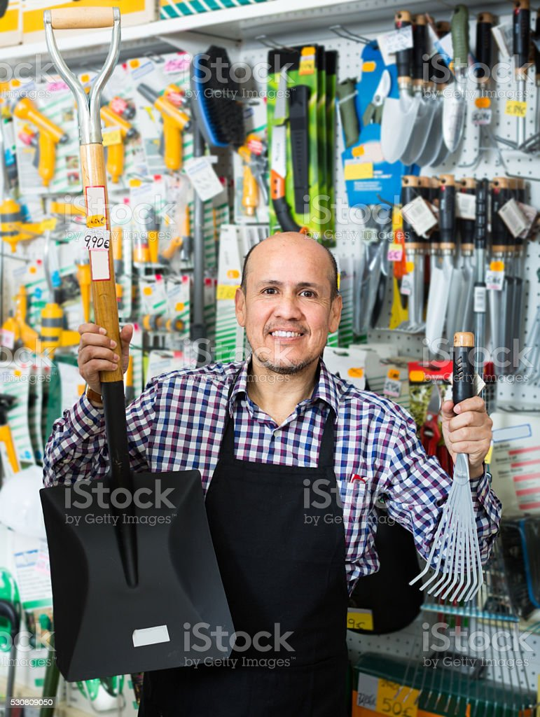 seller smiling at gardening section stock photo