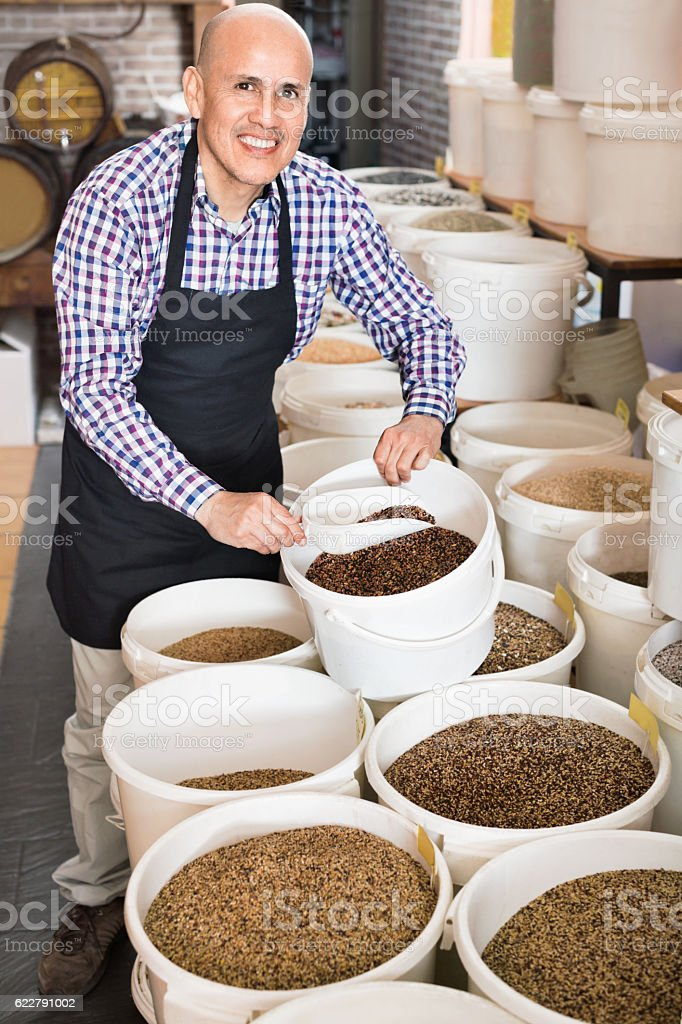Seller taking bird seeds with scoop from bucket stock photo