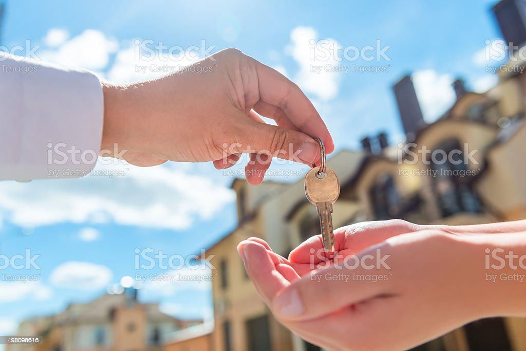 seller transfers key to the house in hands of buyer stock photo