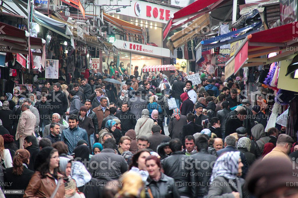 Sellers and buyers in crowd at a shopping street market stock photo