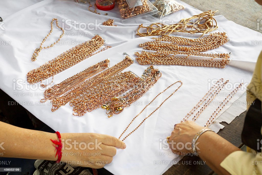 Selling and inspecting red gold jewelries royalty-free stock photo