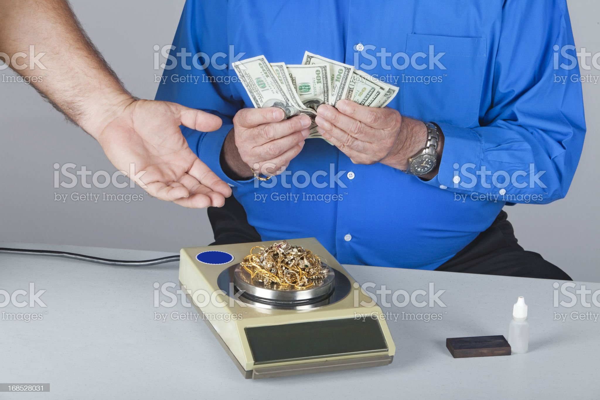 selling scrap gold on a penny weight scale royalty-free stock photo