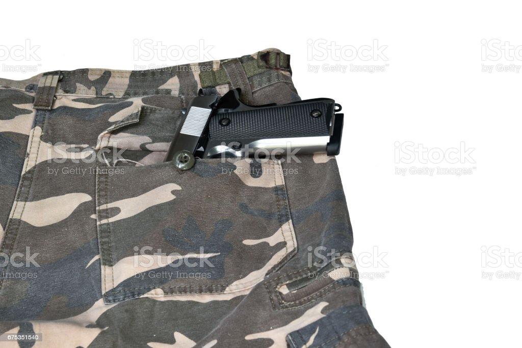 1911 semi automatic handgun in camouflage pant pocket white background stock photo
