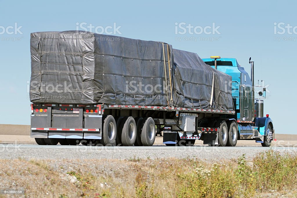 Semi Flatbed Truck Hauling A Covered Load On Interstate Highway stock photo