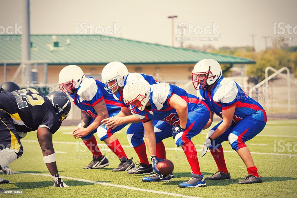 Semi pro football players lined up before play during game stock photo