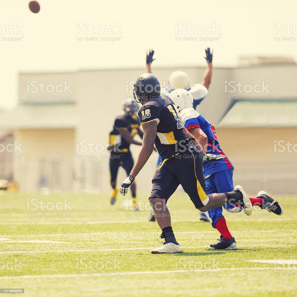 Semi professional football players running to intercept ball during game stock photo