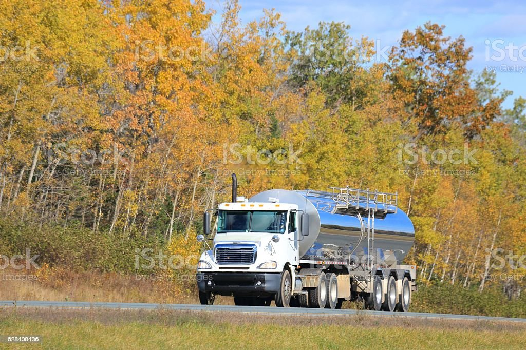 Semi tanker on an interstate highway, trees in background. stock photo