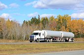 Semi tanker on an interstate highway, trees in background.