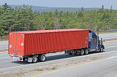 Semi Tractor Trailer Truck Hauling A Large Shipping Container