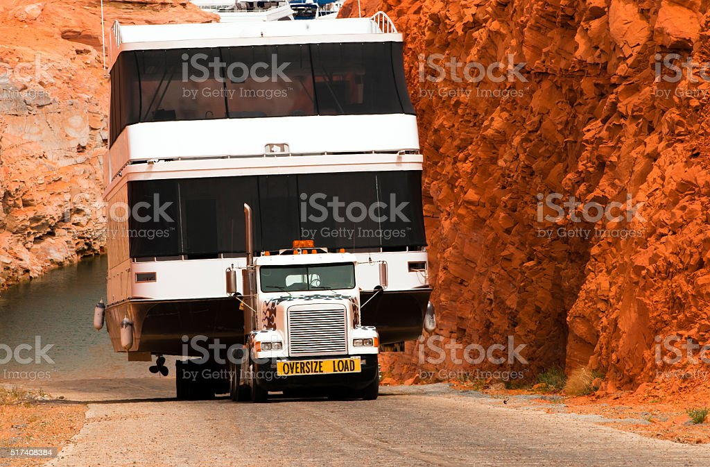 Semi truck and boat on flat bed trailer Page marine stock photo