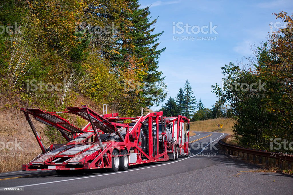 Semi Truck Car Hauler Red trailer on autumn winding road stock photo