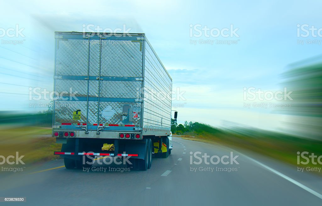 Semi truck cruising down the highway with a speed blur stock photo