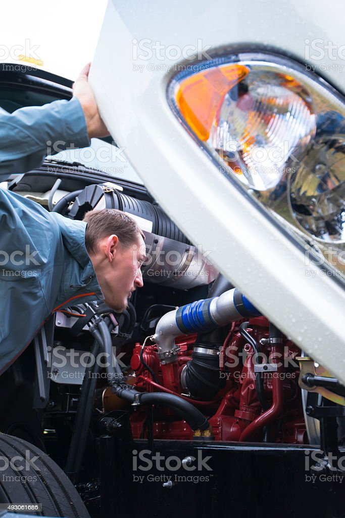 Semi truck driver inspect working engine of white big rig stock photo