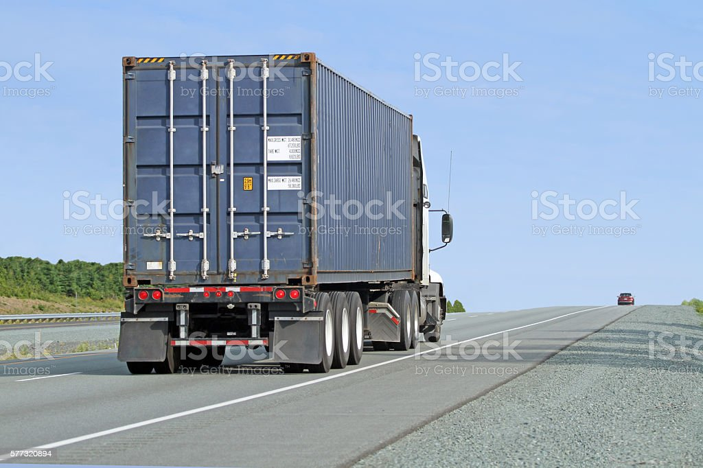 Semi Truck Hauling A Large Shipping Container On Interstate Highway stock photo