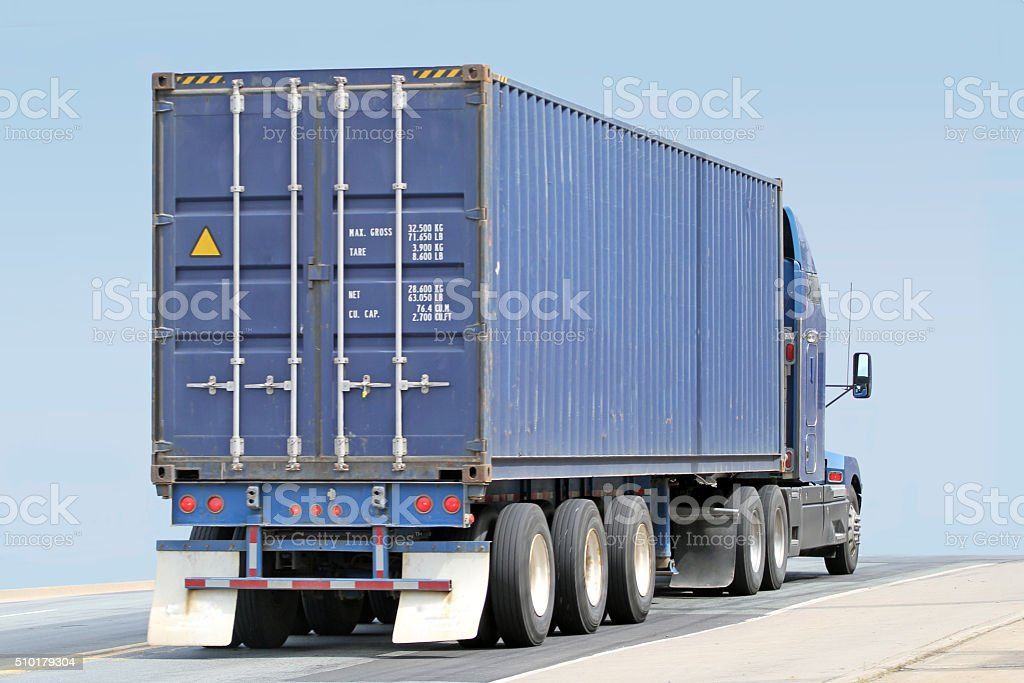 Semi Truck Hauling A Large Shipping Container stock photo