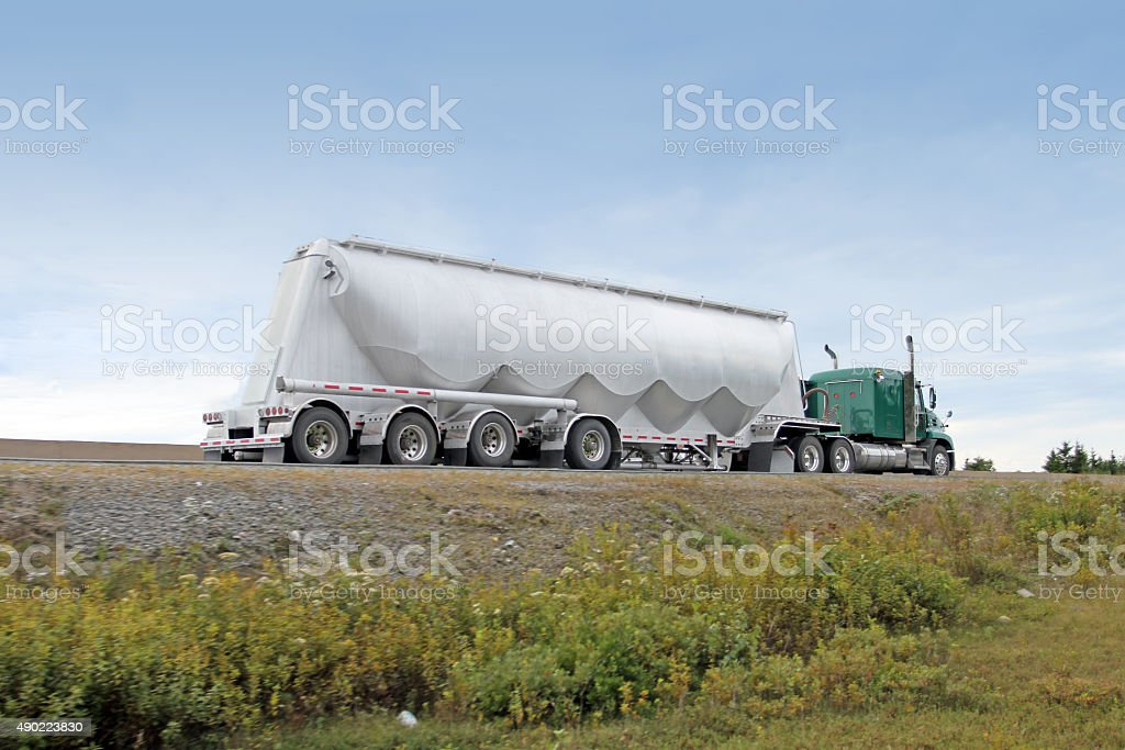 Semi Truck Hauling A Pneumatic Tank Trailer On The Highway stock photo