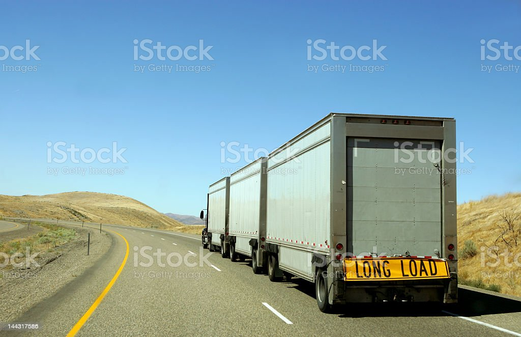A semi truck on a long, winding road under a clear, blue sky royalty-free stock photo