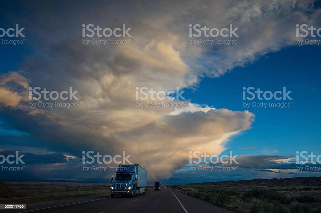 Semi Truck on American Highway Dramtic Twilight Sky stock photo