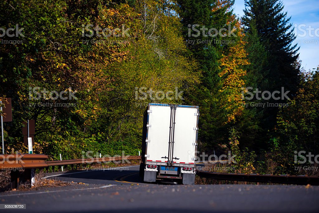 Semi truck trailer back view on winding autumn forest road stock photo