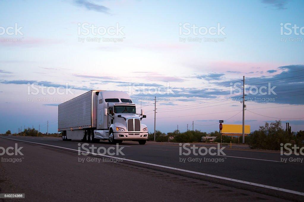 Semi truck trailer going on Arizona road in sunset stock photo