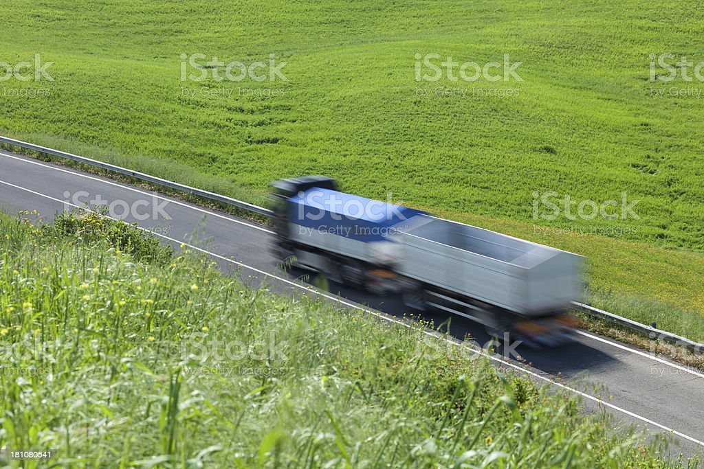 Semi Truck With Trailer Driving Down Road Between Green Fields stock photo