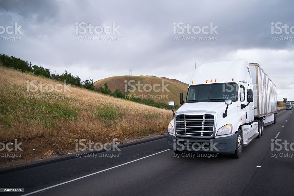 Semi trucks convoy moves interstate highway in California stock photo