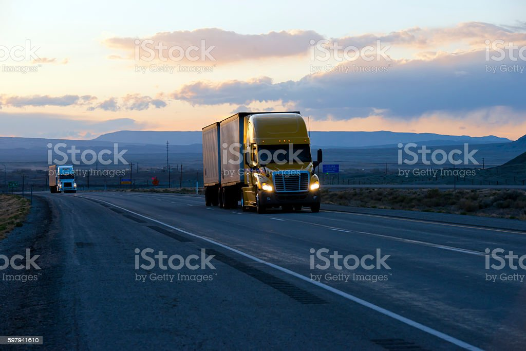Semi trucks on highway in dark twilight evening stock photo