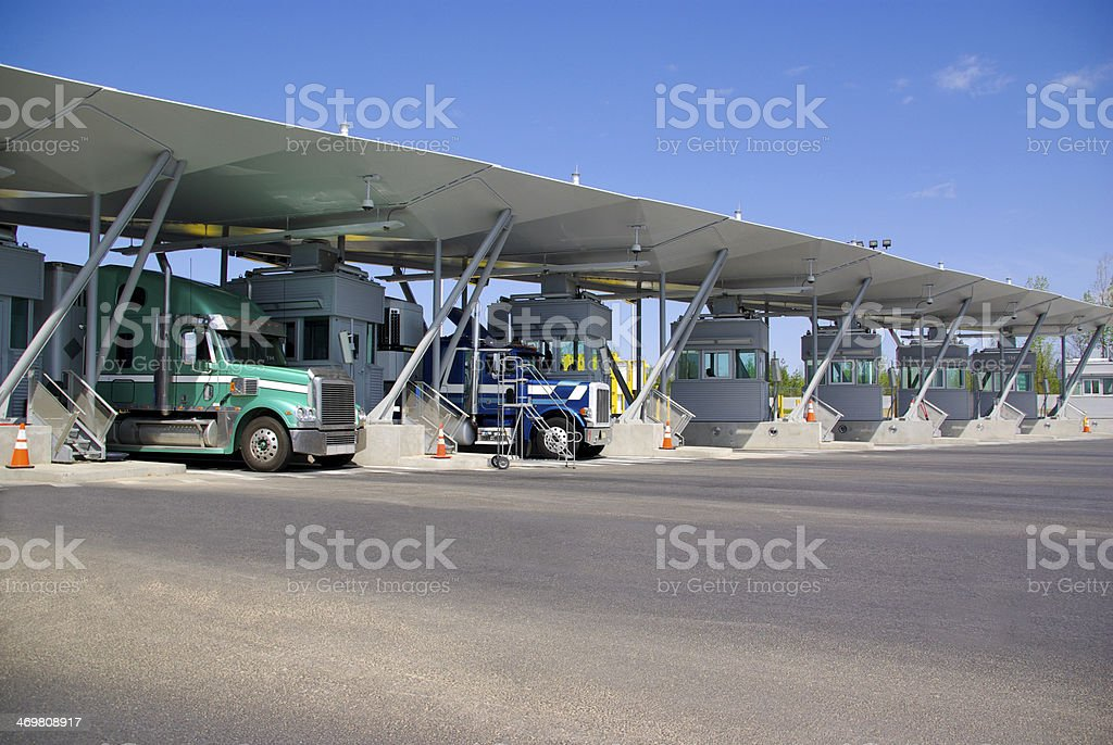 Semi trucks pay at tollbooth at Canadian border stock photo