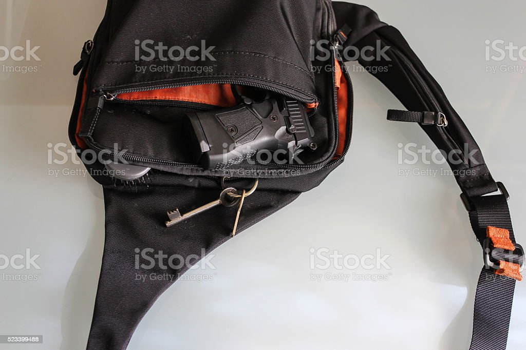 Semi-automatic handgun lying over a handbag, Cal 38 pistol. stock photo