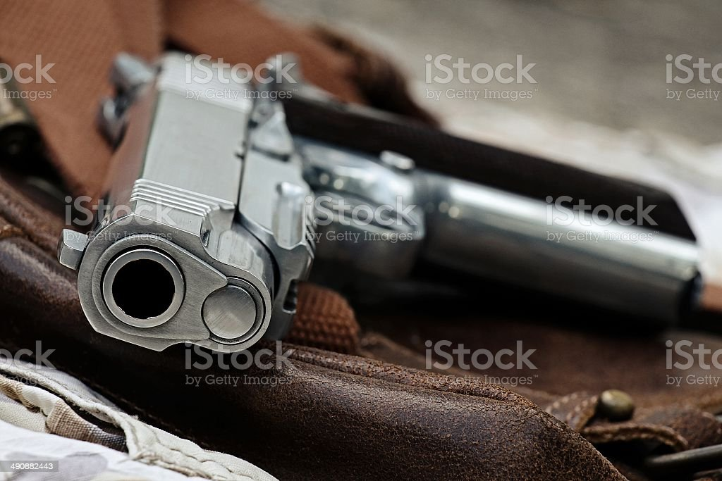 Semi-automatic handgun lying over a Leather handbag, .45 pistol stock photo