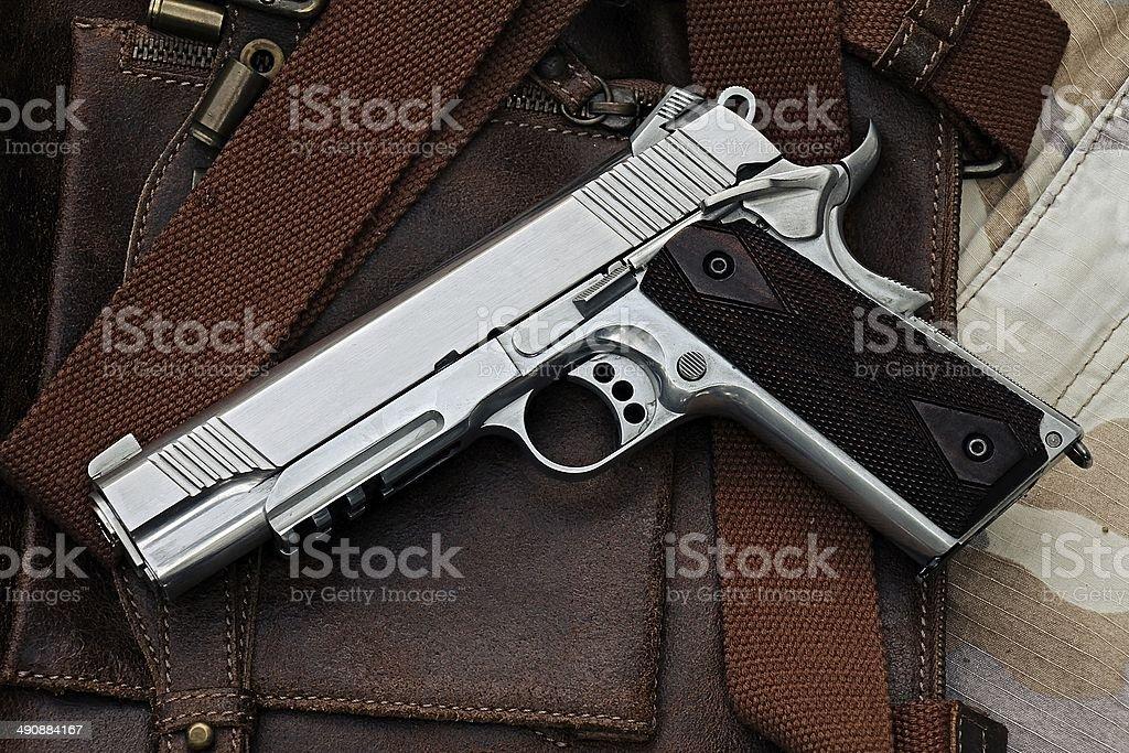 Semi-automatic handgun lying over a Leather handbag, .45 pistol. stock photo