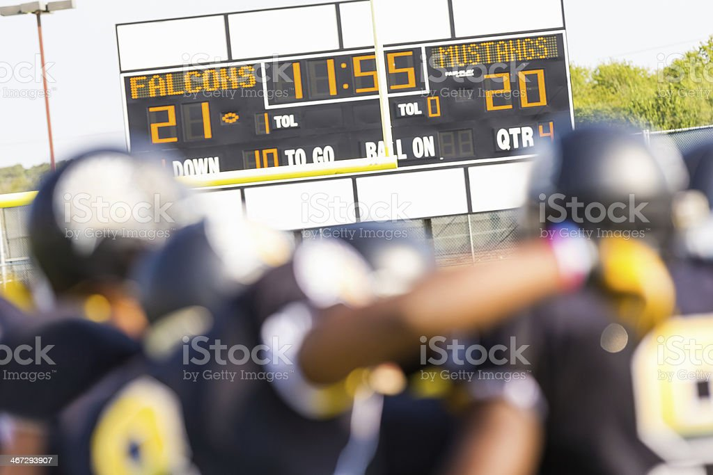 Semi-pro football team players looking at scoreboard after game stock photo