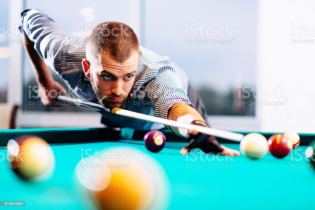 Semi-professional pool game player ready for the shot stock photo