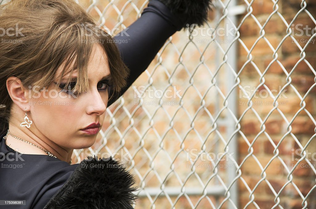 Semi-profile of young woman with chainlink. stock photo