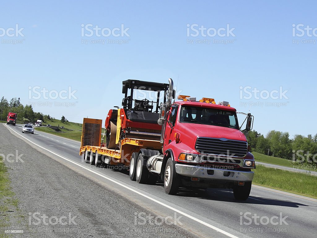 Semi-truck with a steam roller stock photo