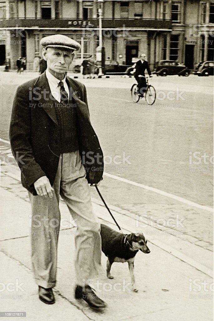 Senior 1930s Style Man Walking Dog Down Street, Vintage royalty-free stock photo
