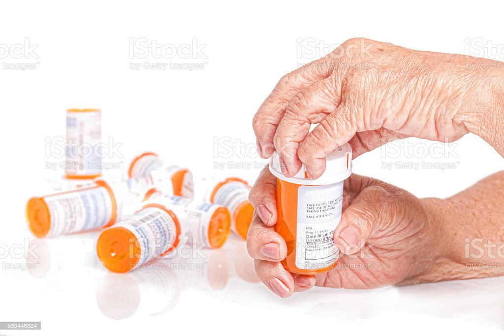 Senior adult , arthritic hands opening a pill bottle stock photo