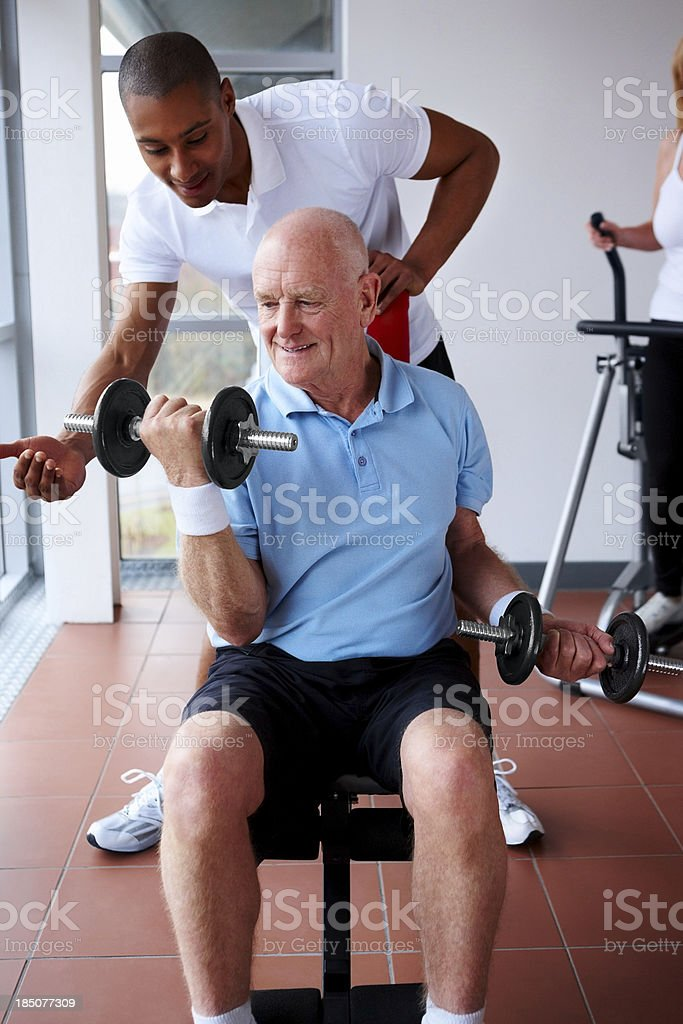 Senior adult assisted by young trainer in gym stock photo