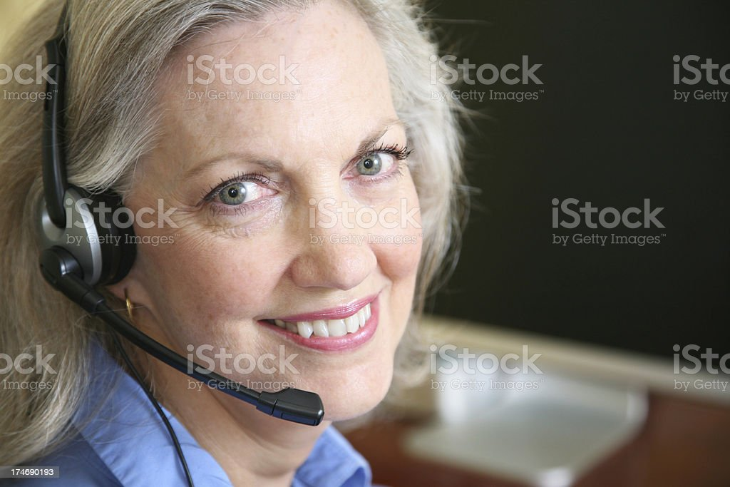 Senior Adult at her Computer with Headset On royalty-free stock photo