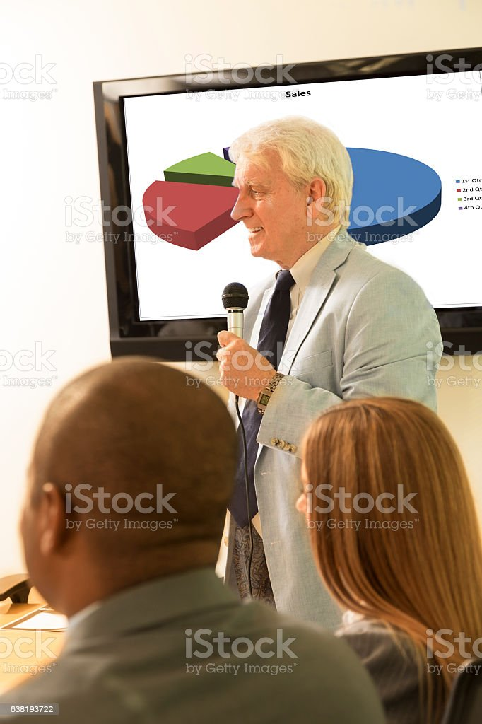 Senior adult business man gives presentation on sales projections. stock photo