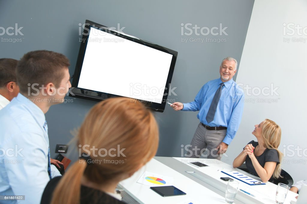 Senior adult businessman gives presentation on sales projections. stock photo