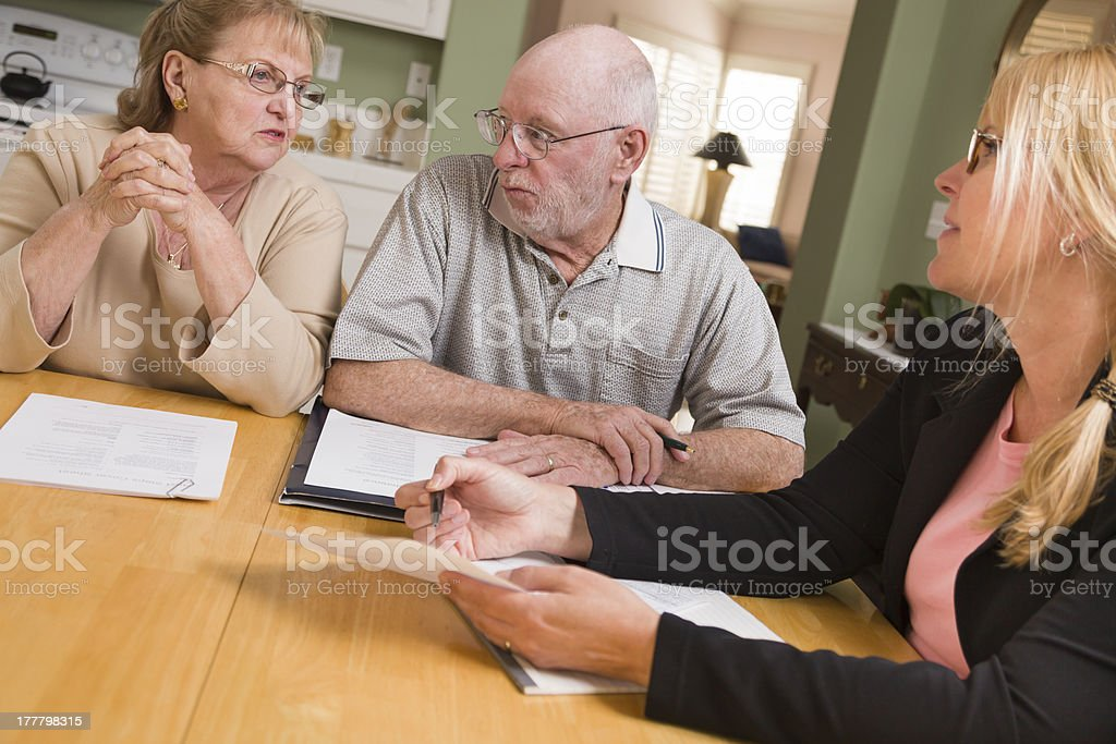 Senior Adult Couple Going Over Papers in Home with Agent royalty-free stock photo