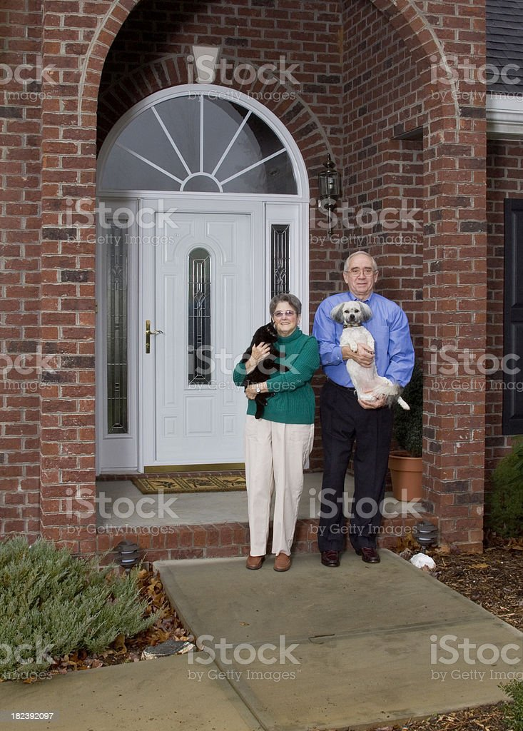 Senior Adult Couple Standing In Front Of House With Pets royalty-free stock photo